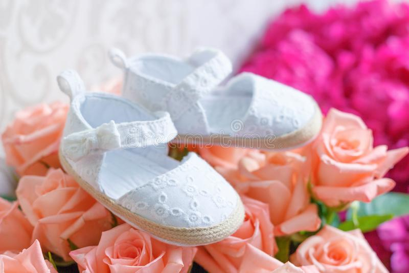 Bouquet des roses et paires de chaussures pour un bébé nouveau-né image libre de droits