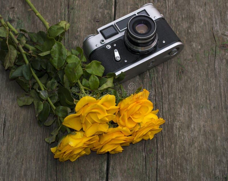 Bouquet des roses jaunes et rétro l'appareil-photo sur une table photographie stock