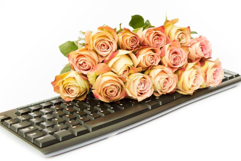 Bouquet des roses roses sur le clavier d'ordinateur images stock