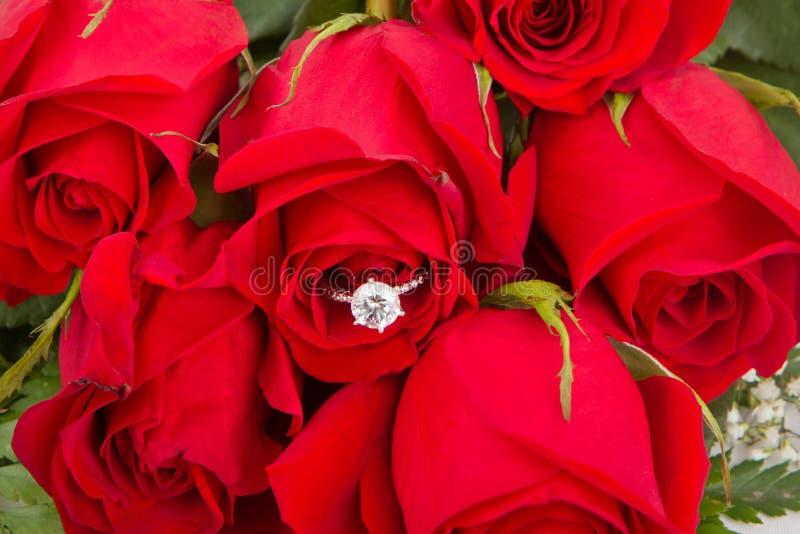 Bouquet des roses rouges avec la bague de fiançailles images stock