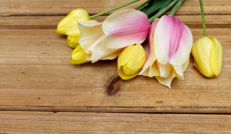 Bouquet des tulipes de rose et de yolow au-dessus de table en bois L'espace heureux de copie de f?te des m?res de carte de voeux  photo libre de droits
