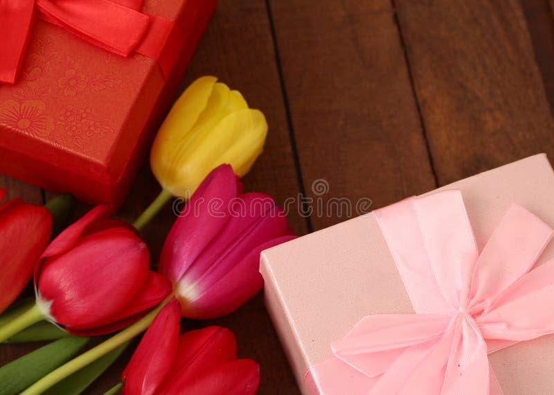 Bouquet des tulipes et des boîte-cadeau sur un fond en bois de table photo libre de droits