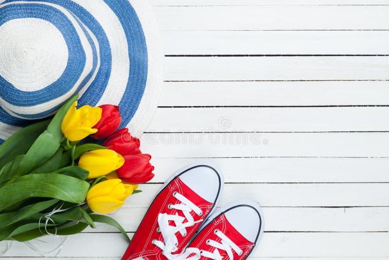 Bouquet des tulipes et des chaussures en caoutchouc avec le chapeau bleu photographie stock