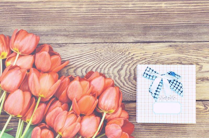 Bouquet des tulipes fraîches avec un cadeau images stock