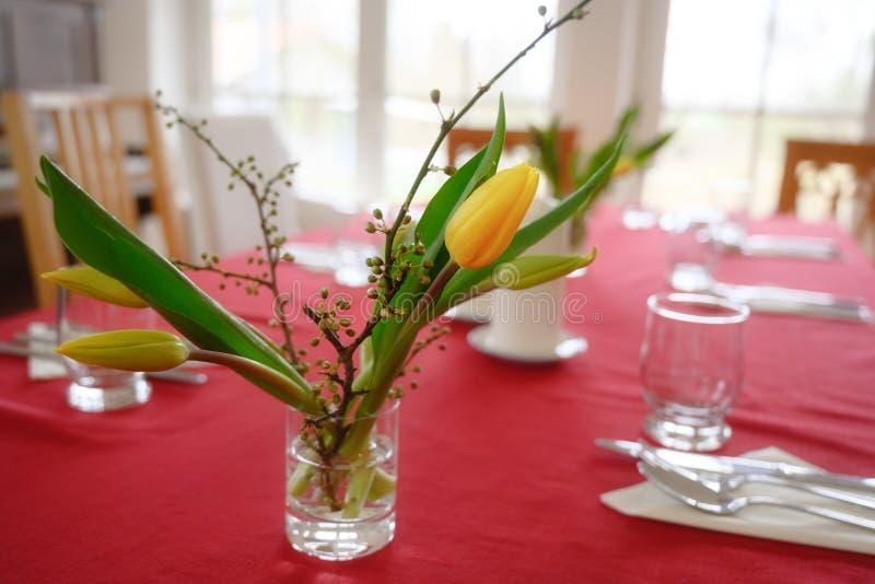 Bouquet des tulipes jaunes sur une table réglée occasionnelle avec la nappe rouge photos libres de droits