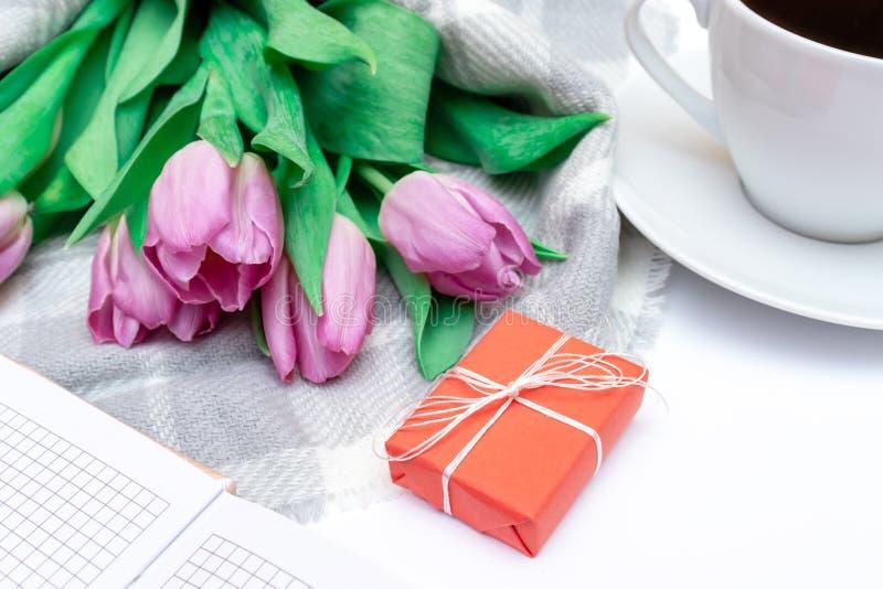 Bouquet des tulipes lilas roses coupées avec un boîte-cadeau rouge et une tasse de café noir sur la fin blanche de fond  image stock