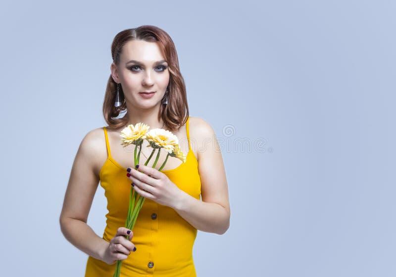 Bouquet di giovane donna caucasica tranquil posa con fiori fotografia stock