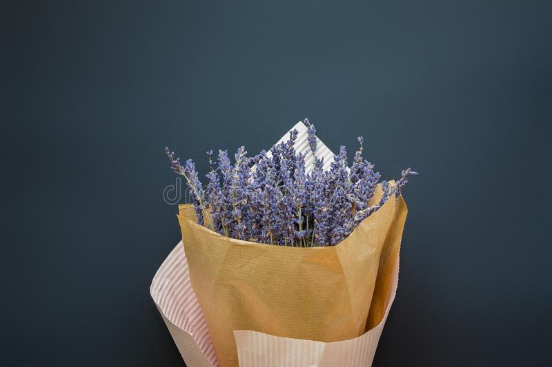A bouquet of dry lavender in kraft paper on a dark background, symbolizing summer and France. Flat lay, top view. A bouquet of dry lavender in kraft paper on a royalty free stock photo