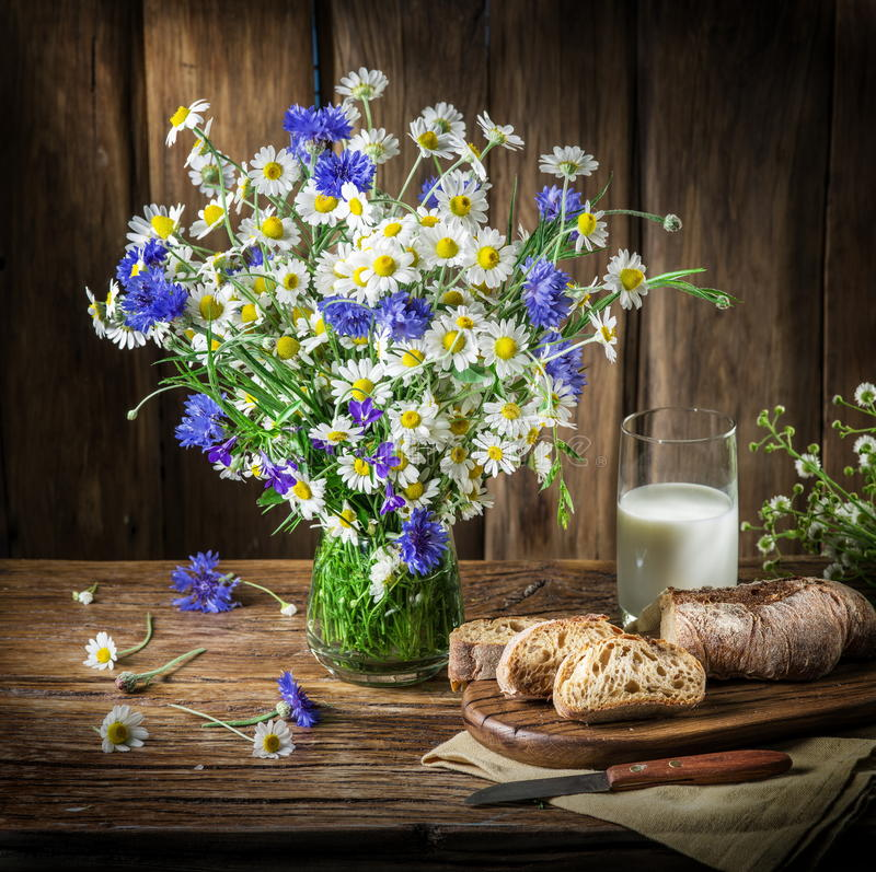 Bouquet of field flowers, glass of milk and soft bread. royalty free stock photography