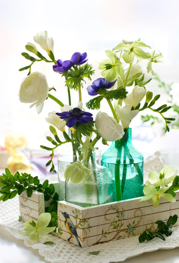 Bouquet of flowers. Ranunculus, anemone, freesia and hellebore in glass bottles royalty free stock photography