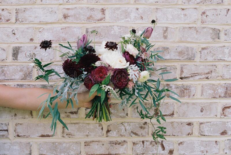 Bouquet of flowers against brick wall stock photos