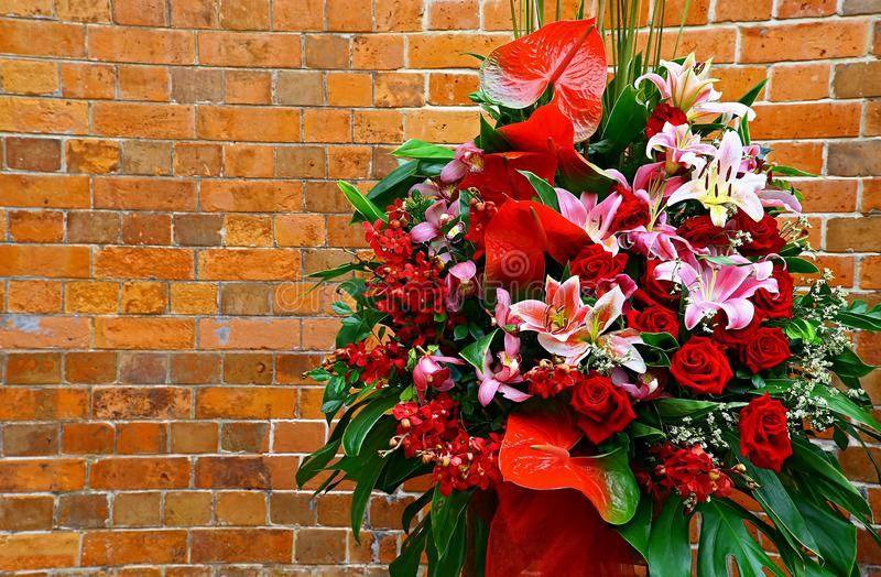 Bouquet flowers against curvy brick wall stock photo