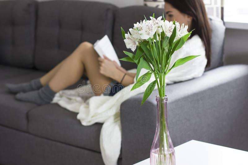 Bouquet of flowers Alstroemeria in vase on background of reading woman royalty free stock image