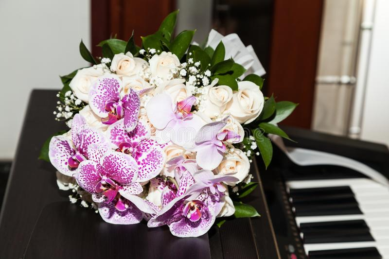 Bouquet of flowers of the bride on her wedding day on the piano royalty free stock photo