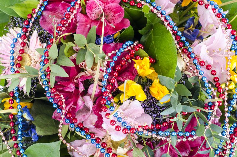 Bouquet of flowers and colored beads for Mardi gras. Studio Photo royalty free stock photos