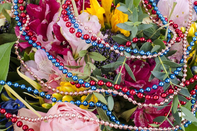 Bouquet of flowers and colored beads for Mardi gras. Studio Photo royalty free stock images