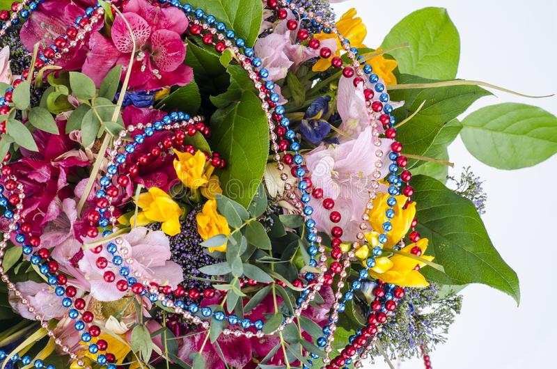 Bouquet of flowers and colored beads for Mardi gras. Studio Photo stock photo