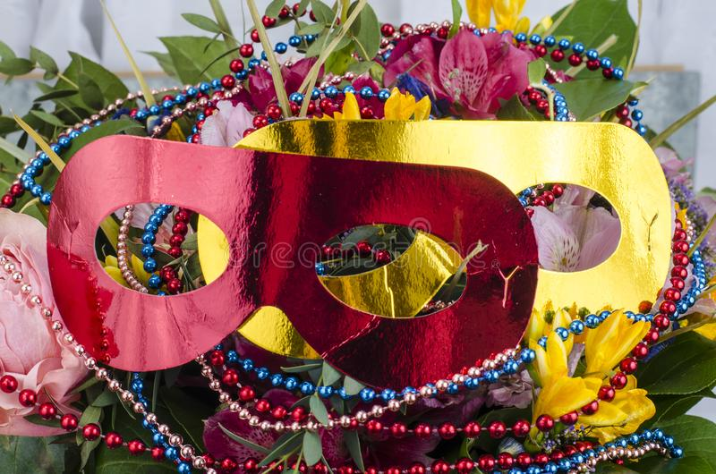 Bouquet of flowers and colored beads for Mardi gras. Studio Photo stock images