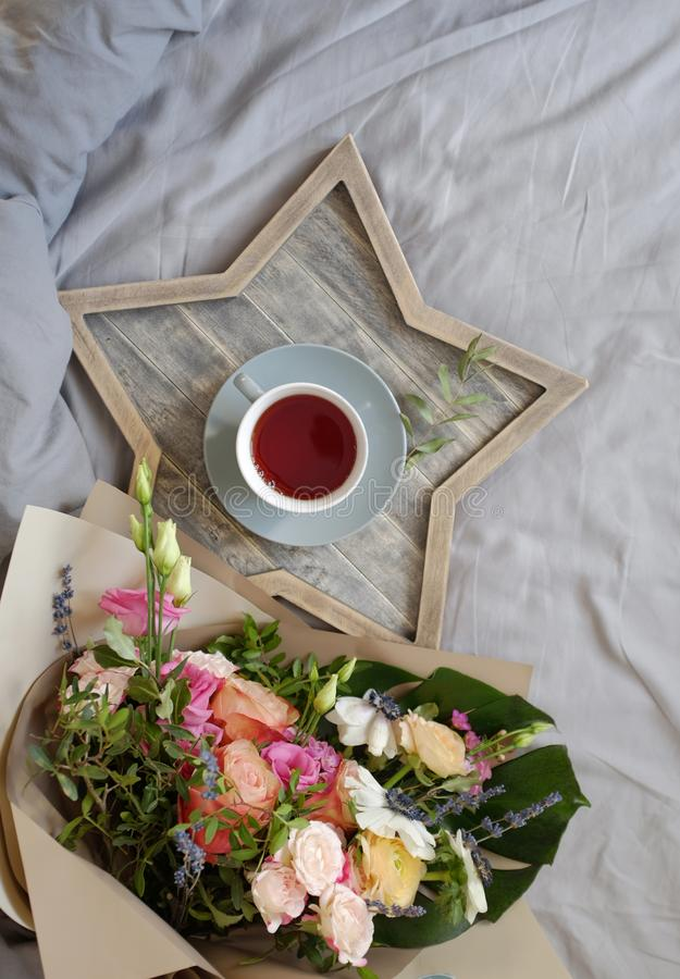 Bouquet of flowers and a cup of tea on a gray background. Top view stock photo