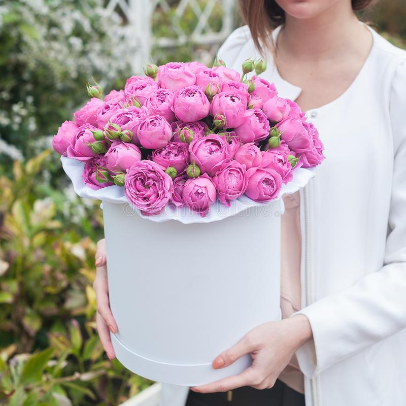 A bouquet of flowers in a hat box in the girl`s hands stock image