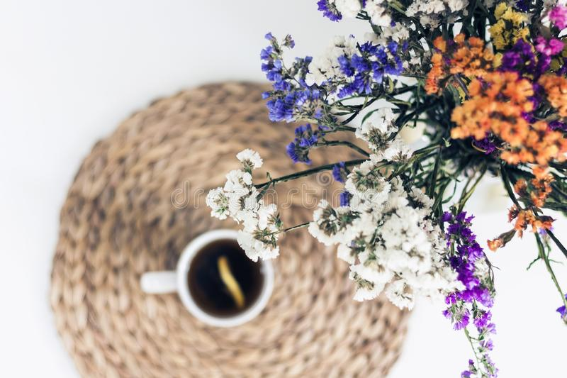 Bouquet of flowers, lemon tea in a white ceramic cup on a straw wicker stand on the table, top view stock photography