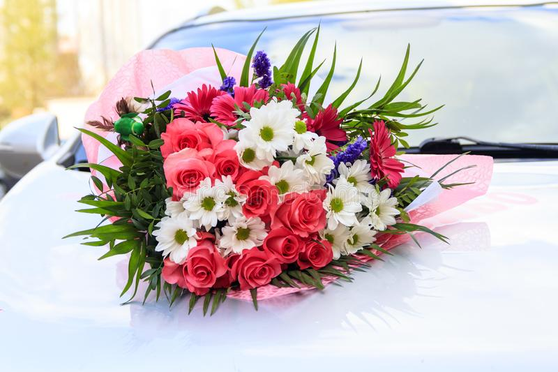 A bouquet of flowers is located on the car. natural lighting. flowers of roses and daisies royalty free stock photo
