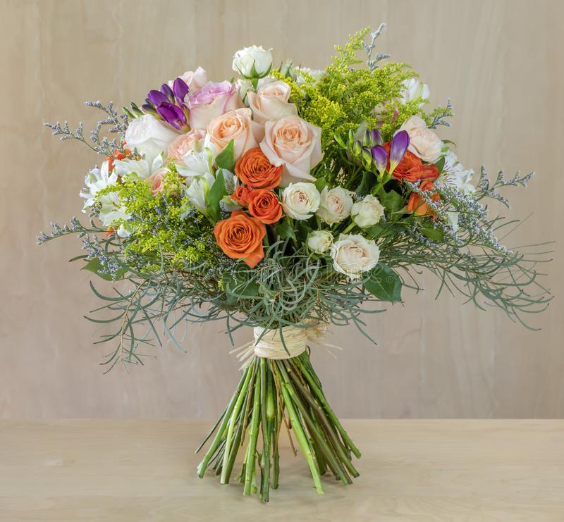 Bouquet of flowers, multi-colored roses with green leaves royalty free stock photography