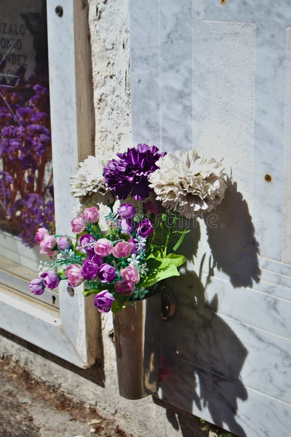 A bouquet of flowers next to a niche on a sunny day. A bouquet of flowers show the duel in a niche in a cemetery shortly before All Saints& x27; Day in royalty free stock photos