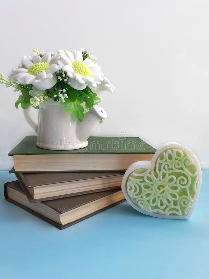Bouquet of flowers on old books, decorative heart on blue desk on white background. Bouquet of flowers in a vase, stack of books, decorative heart,  on blue royalty free stock images