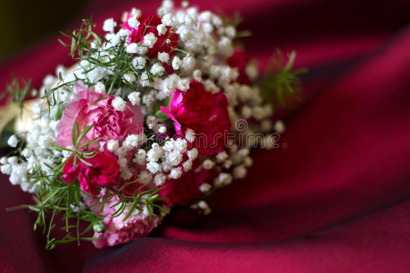 Bouquet of flowers on red fabric romantic love floral background concept. Closeup royalty free stock image