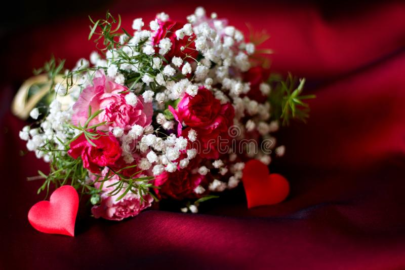 Bouquet of flowers on red fabric romantic love valentine`s day floral background concept with heart shape. Closeup stock images