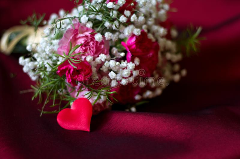 Bouquet of flowers on red fabric romantic love valentine`s day floral background concept with heart shape. Closeup stock image