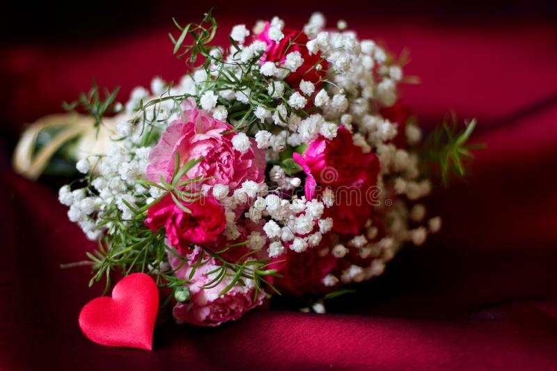 Bouquet of flowers on red fabric romantic love valentine`s day floral background concept with heart shape. Closeup royalty free stock images