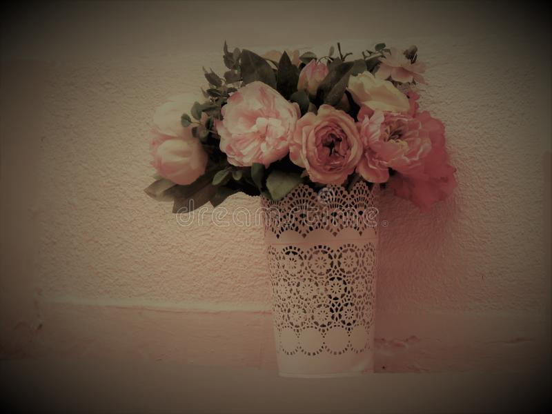 Bouquet of flowers with roses, in a vase with a paper cuff, arranged in front of a pink environment stock photos
