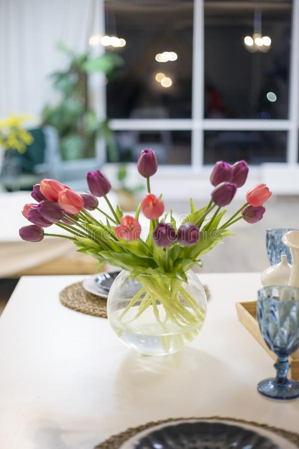Bouquet of flowers from tulips in a vase on a table against the background of a window indoors royalty free stock image