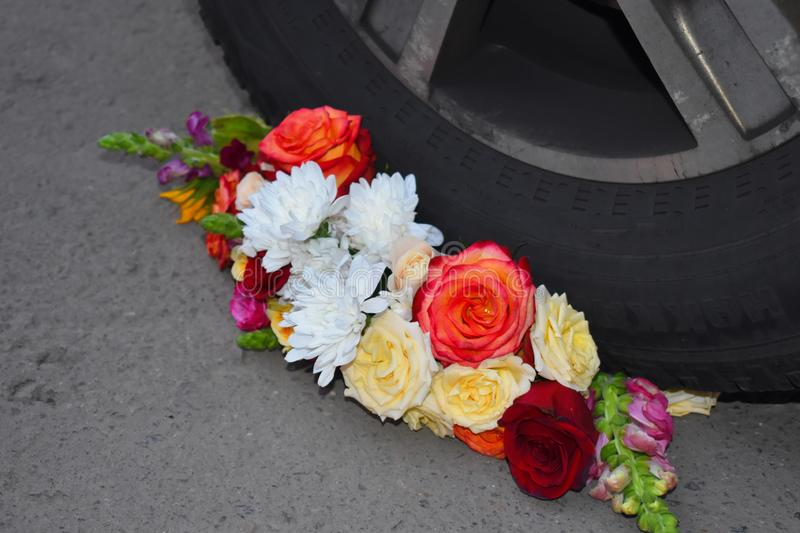 A bouquet of flowers under the wheel of a car. Crushed and broken love stock image