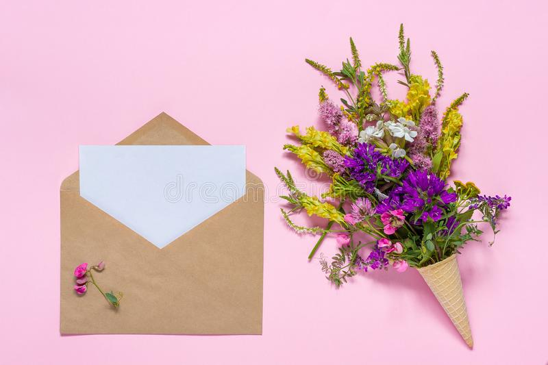 Bouquet flowers in waffle cone and craft envelope with paper card stock photography