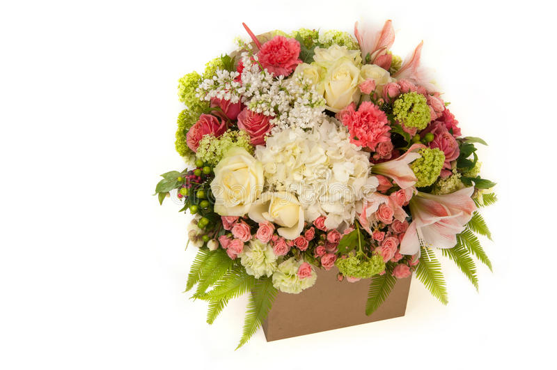 A bouquet of flowers on a white background. Flowers roses and carnation in cardboard box on a white background. Valentine`s Day stock photos