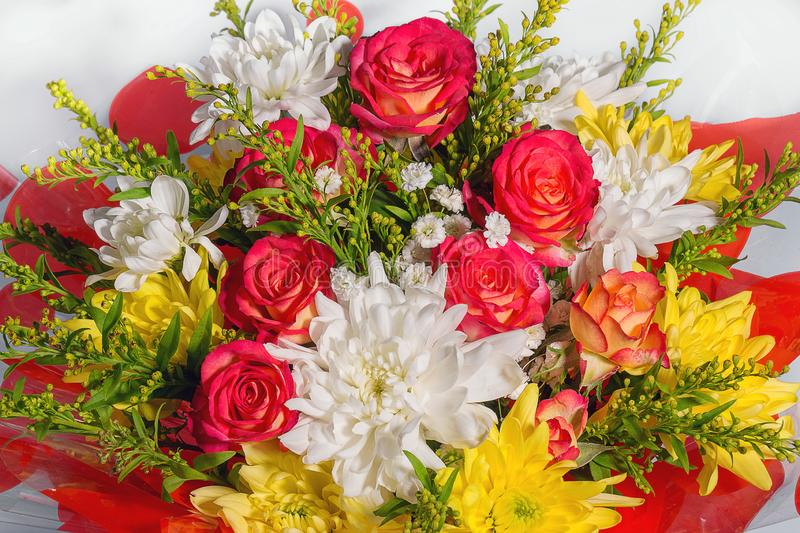 Flower arrangement of red roses and chrysanthemums royalty free stock photo