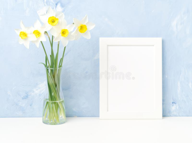 Bouquet of fresh flowers, white frame on table, opposite blue textured concrete wall. Empty space for text. Mock up. stock images