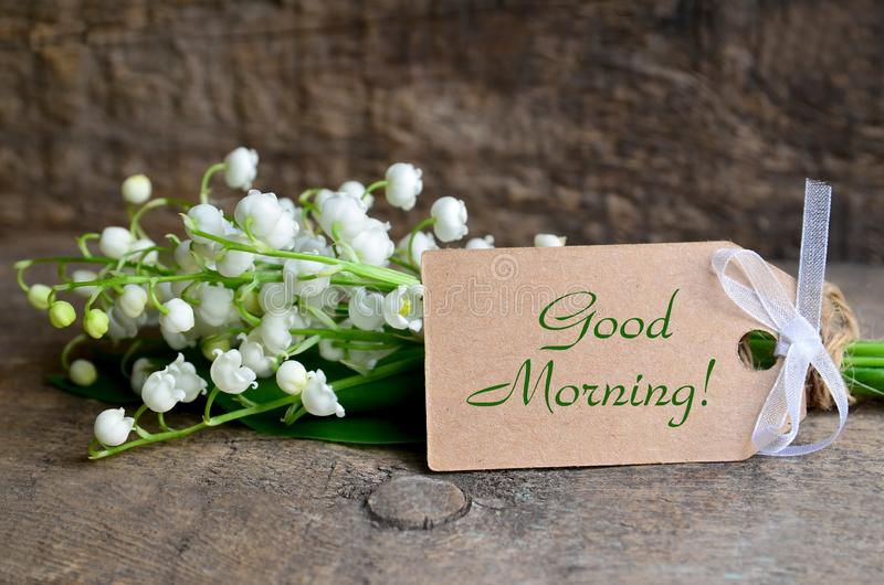 Bouquet of fresh lily of the valley flowers and tag card with a Good Morning inscription on old wooden table. stock photo