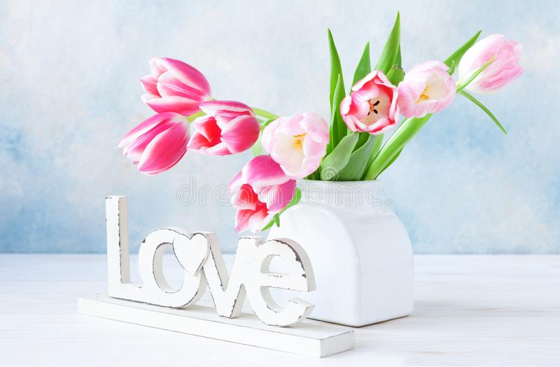 Bouquet of fresh pink tulips in vase on sky blue background. Concept for Valentine`s day, wedding, engagement, mother`s day, Mar stock photography