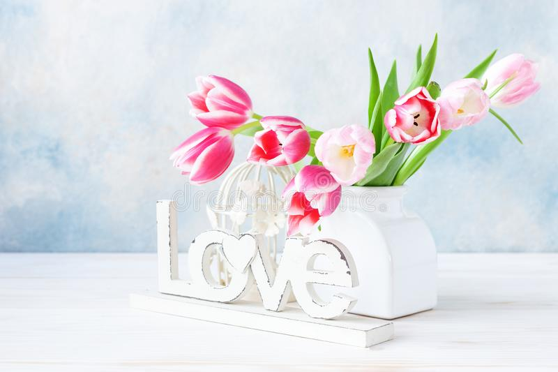 Bouquet of fresh pink tulips in vase on sky blue background. Concept for Valentine`s day, wedding, engagement, mother`s day, Mar stock image