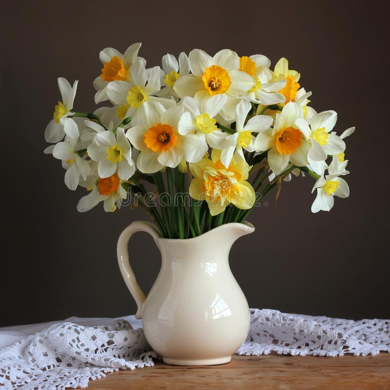 Bouquet of garden daffodils in a white jug. narcissus. stock photo