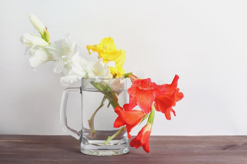 Bouquet of gladioli in a glass vase on a wooden table royalty free stock photo