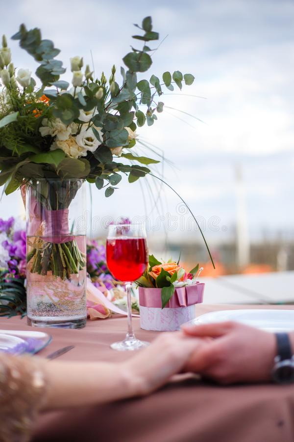 A bouquet in a glass vase, a glass of wine, a small gift, the intertwined hands of a man and a woman. Date, picnic for two, a bouquet in a glass vase, a glass of stock photography