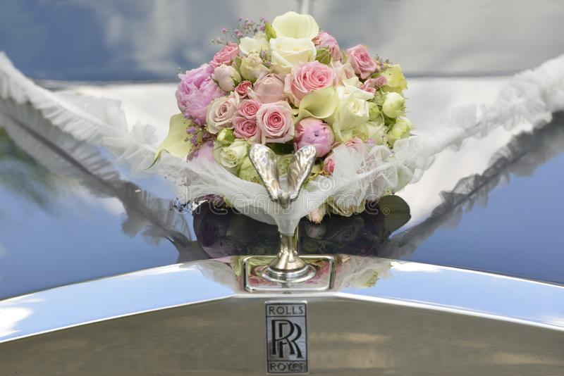 Bouquet on the hood of the wedding car stock photography