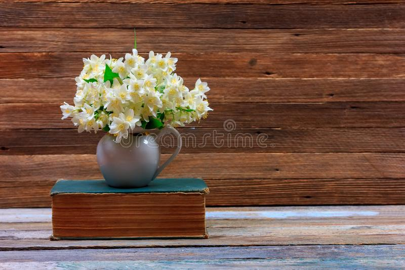 Bouquet of Jasmine flowers in a jug on an old book on a table on a brown wooden retro background. With copy space royalty free stock image