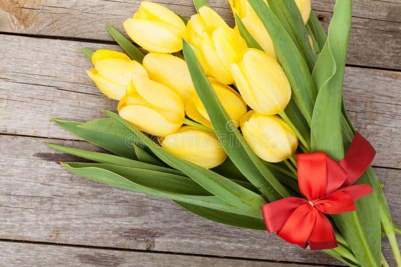 Bouquet jaune frais de tulipes au-dessus de fond en bois de table photo libre de droits