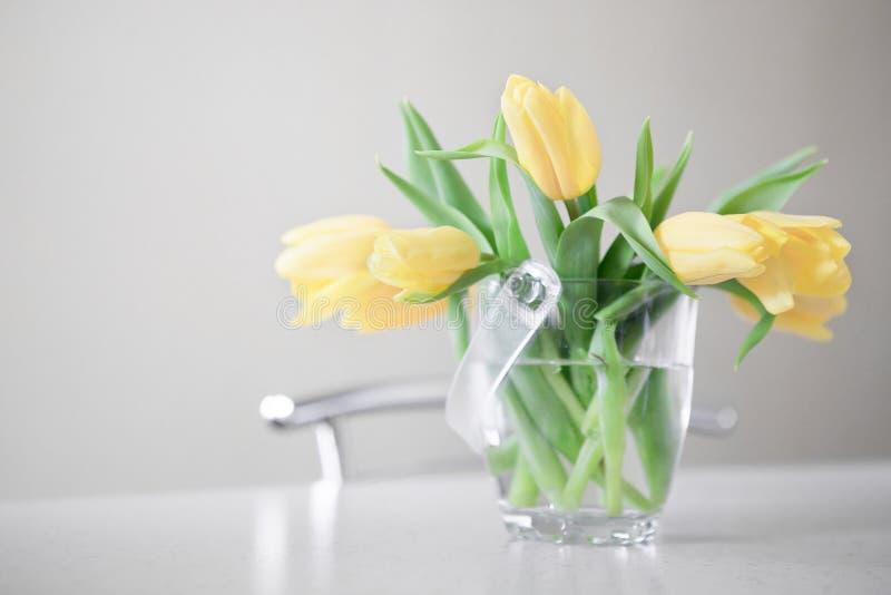 Bouquet jaune frais de tulipes au-dessus de table en bois Sur le blanc images stock